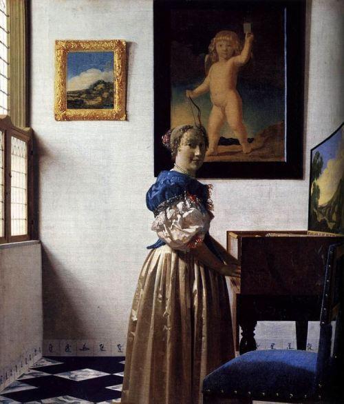 Femeie stand langa un cembalo